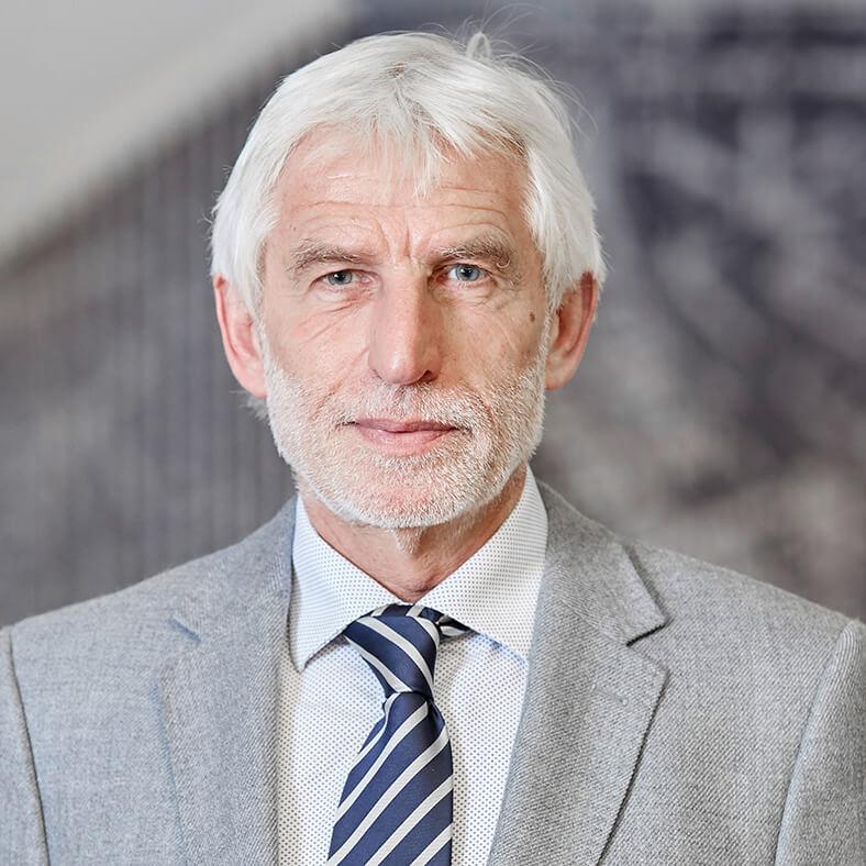 Porträt von Dr. Bernhard Ascherl. Er hat kurze, weiße Haare und einen Vollbart, trägt einen hellen Anzug mit hellem Hemd und dunkler Krawatte.