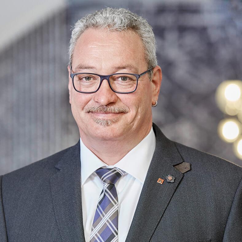 Porträt von Hans-Peter Kern. Er hat kurze, graue Haare, einen Schnauzbart, trägt eine Brille, einen dunklen Anzug mit hellem Hemd und Krawatte.