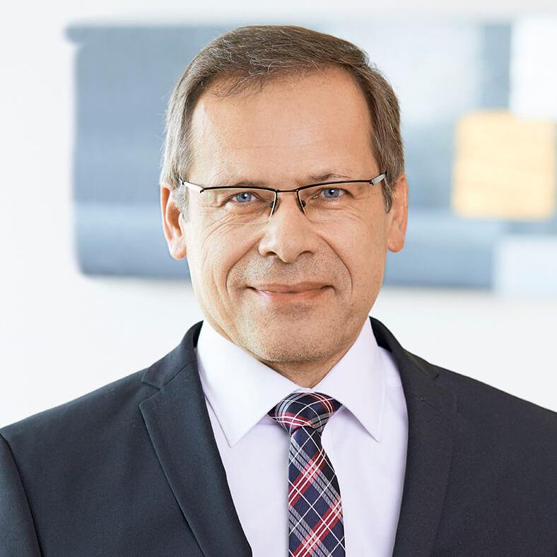 Porträt von Johannes Tichi. Er hat kurze dunkle Haare, trägt eine Brille und einen Anzug mit hellem Hemd und rot-blauer Krawatte.