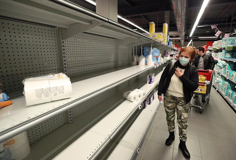 Eine Frau mit Mund-Nasen-Schutz steht in einem Supermarkt neben einem leeren Regal für Toilettenpapier.