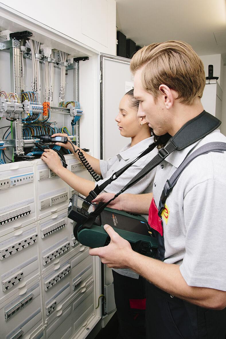 Ein Mann und eine Frau stehen vor einem offenen Schaltkasten und prüfen mit einem Messgerät Elektroleitungen.