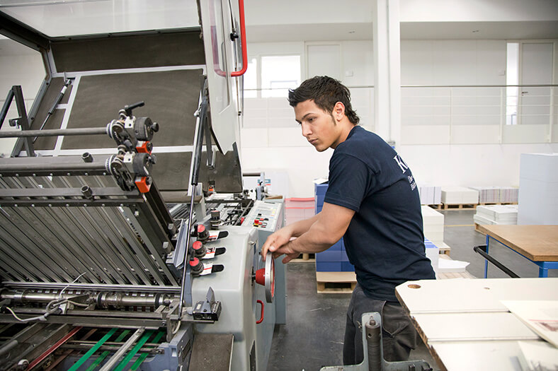 Ein mann steht an einer Druckmaschine und bedient einen Drehregler.
