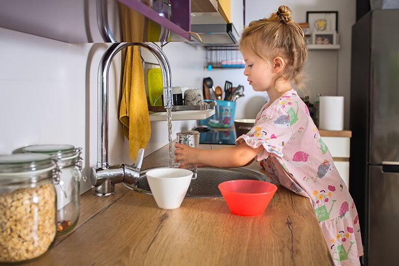 Ein Mädchen im Grundschulalter füllt ein Glas Wasser an einem laufenden Wasserhahn in der Küche.