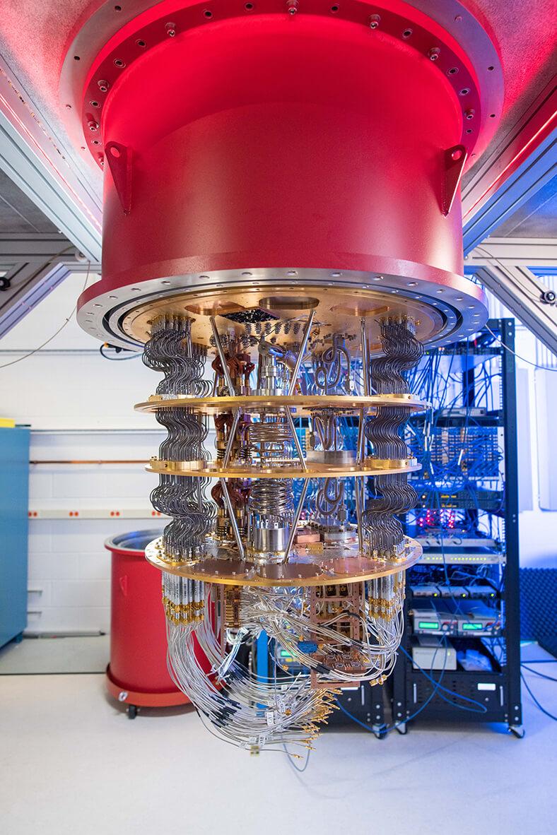 Das Bild zeigt den Quantencomputer von Google, Man sieht einen hängenden roten Zylinder, aus dem nach unten viele gebogene Leitungen führen, segmentiert von mehreren runden Scheiben. Im Hintergrund stehen Regale mit weiteren elektronischen Geräten