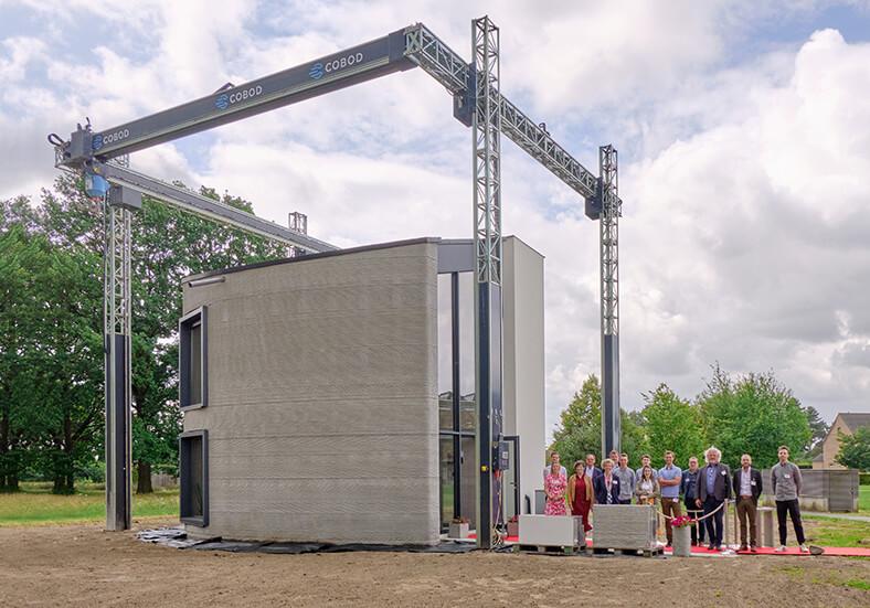 3-D-Betondrucker im Freien mit einem gedruckten Haus, rechts daneben steht eine Gruppe von mehreren Menschen.