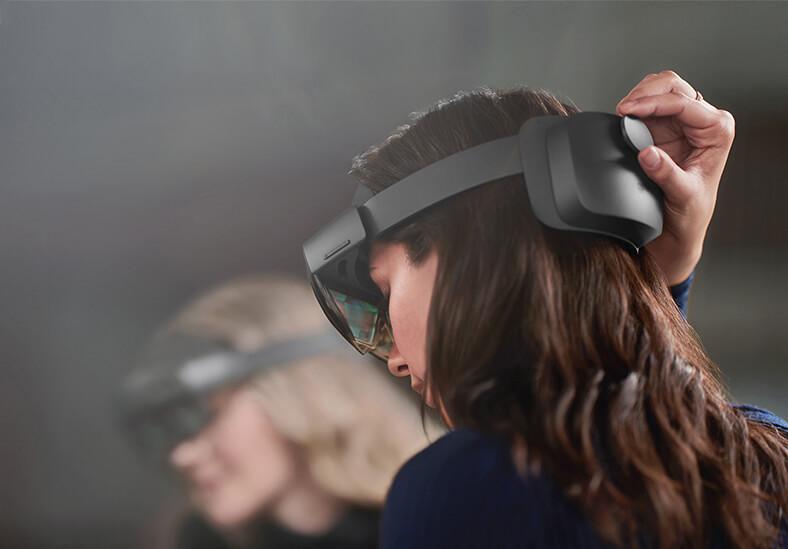 Frauenkopf mit dunklen Haaren von hinten, mit einer Augmented Reality Datenbrille.