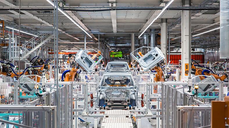 VW-Werk in Zwickau, Werkshalle mit Robotern, die Autoteile zusammensetzen.