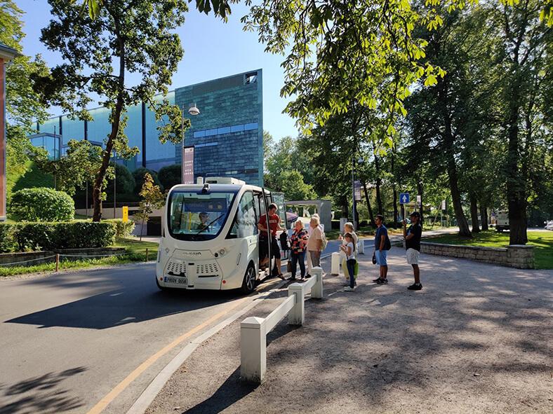 Ein weißer Bus ohne Fahrer steht auf einer Straße in Tallinn (Estland); ein junger Mann in kurzer Hose und T-Shirt steigt aus. Rechts steht eine Schlange von mehreren Menschen, die einsteigen wollen.