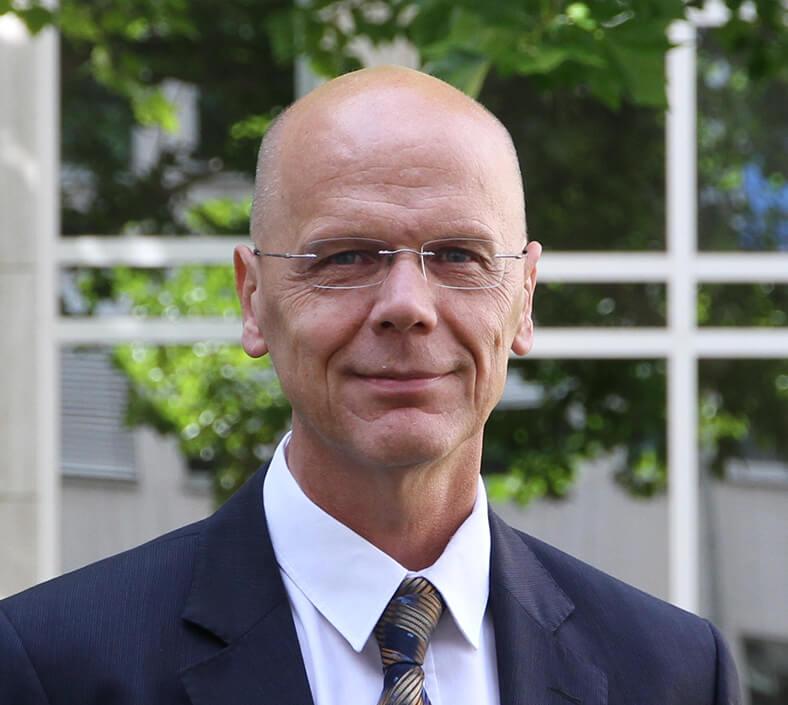 Porträt von Dr. Hüdepohl. Er hat eine Halbglatze, trägt eine Brille und einen dunklen Anzug mit Krawatte und weißem Hemd. Er steht im Freien, im Hintergrund sieht man die Fenster eines Gebäudes.