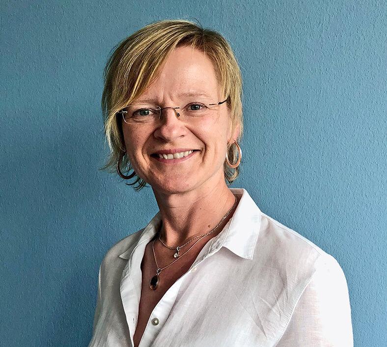 Porträt von Irina Michelsen. Sie hat kurze blonde Haare, trägt eine Brille und eine weiße Bluse.