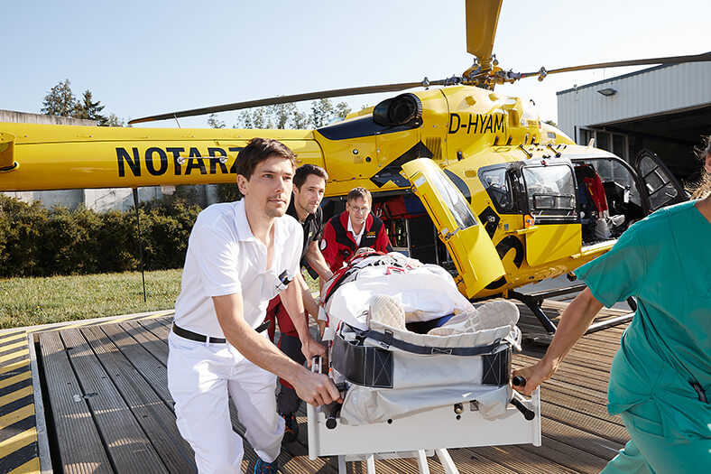 """Ein Verletzter wird von vier Männern auf einer Bahre in die Notaufnahme transportiert. Im Hintergrund steht ein Hubschrauber mit der Aufschrift """"Notarzt""""."""