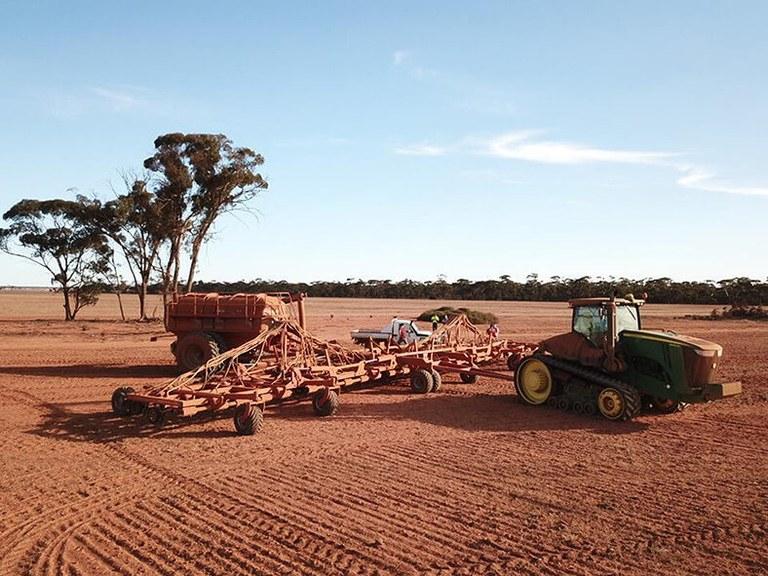 Das Bild zeigt einen Acker mit roter Erde in Australien, darauf ein Traktor und weitere Landmaschinen. Im Hintergrund ist ein Waldrand zu sehen.