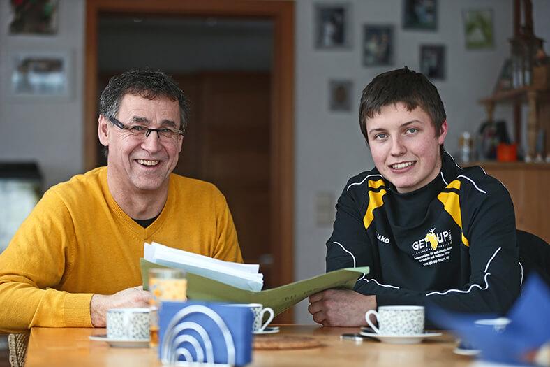 Am einem Tisch sitzen Stefan Mayr (links) und Martin Welte (rechts) vor Kaffetassen. Stefan Mayr hat eine Brille und trägt einen gelben Pullover, Martin Welte trägt eine schwarz-gelbe Trainingsjacke. Sie blättern zusammen in Unterlagen.