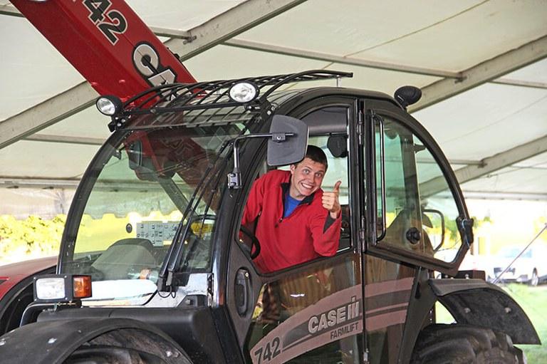 Marvin Welte sitzt in einem großen Traktor in einer Maschinenhalle. Er trägt ein rotes Sweatshirt und lächelt in die Kamera mit erhobenem Daumen.