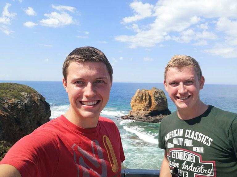 Martin Welte (links) trägt ein rotes T-Shirt, sein Bruder steht rechts neben ihm hat blonde Haare und trägt ein grünes T-Shirt. Im Hintergrund sieht man Meer, Felsen und blauen Himmel.