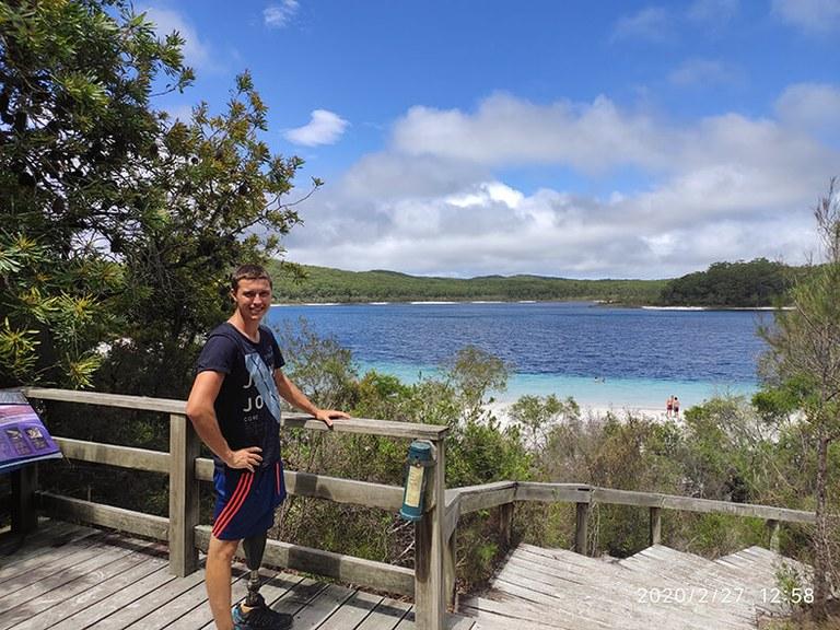 Marvin Welte steht in kurzer Hose und T-Shirt an einem Holzgeländer, sein linkes Bein besteht aus einer Prothese. Im Hintergrund ist eine Meeresbucht mit hügeligem Land zu sehen.
