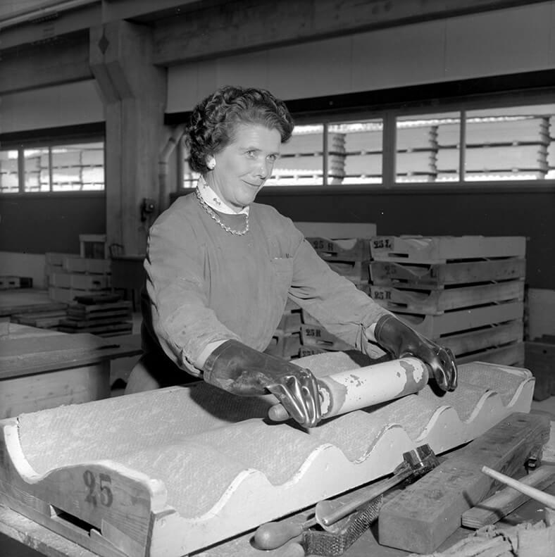 Schwarzweiß-Foto einer Arbeiterin in der Schweiz beim Walzen einer Dachplatte.