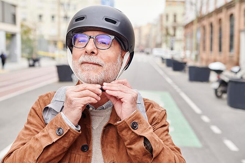 Alterer Mann mit birlle und Vollbart steht auf der Straße und befestigt einen Fahrradhelm auf seinem Kopf.