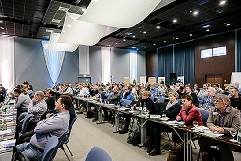 Seminarraum mit Teilnehmern am Forum – Fürhung. Kommunikation. Verhalten. Die Personen sitzten an kleinen Tischen in langen Reihen.