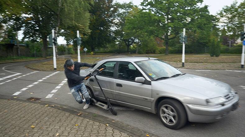 Das Foto zeigt ein Auto, das beim Abbiegen an einer Kreuzung einen E-Scooter schneidet und dessen Sturz verursacht.