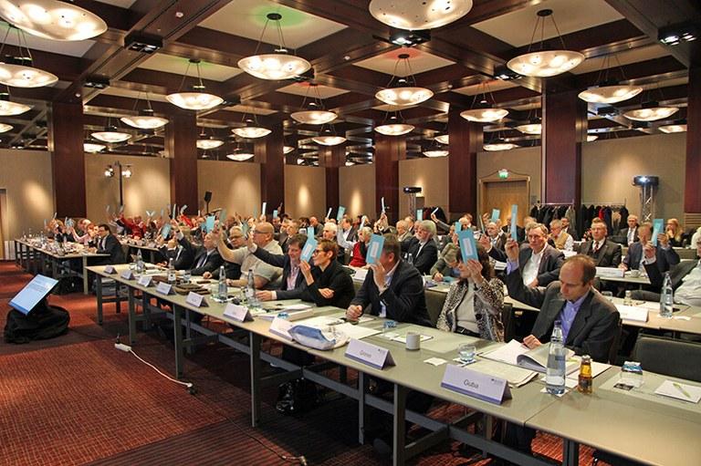 Blick auf die Teilnehmer der Vertreterversammlung der BG ETEM in einem Saal in Köln. Sie sitzen an mehreren langen Tischreihen und strecken für eine Abstimmung blaue Zettel in die Höhe.