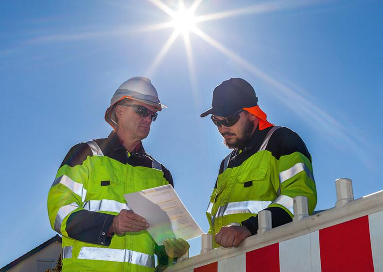 Zwei Arbeiter mit Schutzkleidung, Kopfbedeckung und Sonnenbrille stehen im Freien im Sonnenschein und sehen zusammen auf ein Dokument.