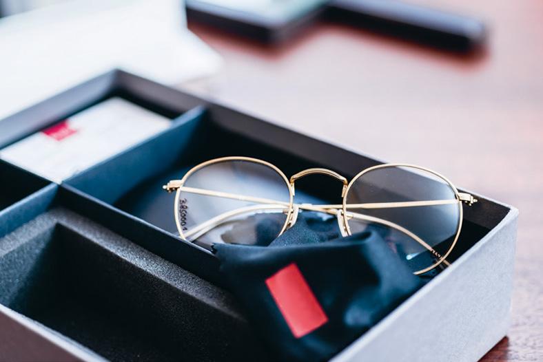 Brille mit Goldrand liegt auf dunkem Tuch in einer Verpackungsschachtel.