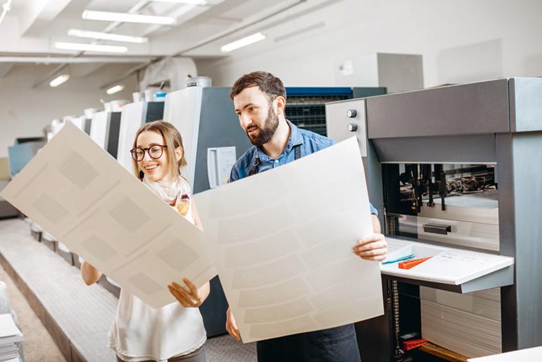 Mann und junge Frau mit Brille stehen in einer Produktionshalle einer Druckerei und halten große Druckbögen in den Händen, auf die sie lächelnd schauen.
