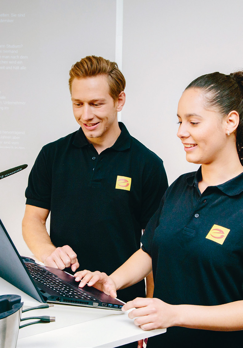 Zwei Kollegen, Mann und Frau, in dunklen T-Shirts, schauen beide auf ein Notebook an einem Stehcounter.