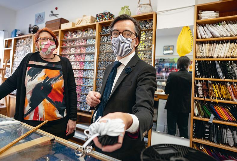 Zwei Verkäufer in einem Einzelhandelsgeschäft für textile Kurzwaren mit bunten Stoffmasken.