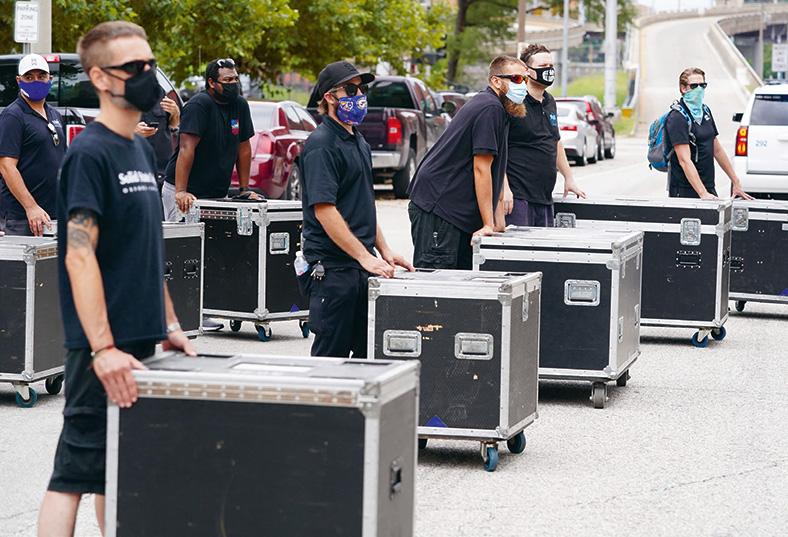 Mitarbeiter für Aufbau von Kulturveranstaltung stehen in dunklen T-Shirts und mit Masken und Sonnenbrillen vor Rollcontainern im Freien.