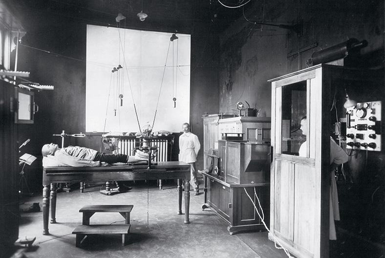 Schwarzweißaufnahme eines Benhandlungsraums, auf einer Liege liegt ein Mann und wird mit einem historischen Gerät geröntgt, ein Arzt steht seitlich im Hintergrund, ein anderer Mitarbeiter bedient das Röntgengerät aus einer Kammer heraus.