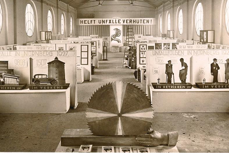 Schwarzweiß-Aufnahme eines Ausstellungsraums mit einem großen Kreissägenblatt im Vordergrund, dahinter rechts und links Stellwände mit Bildern von Unfallfolgen.