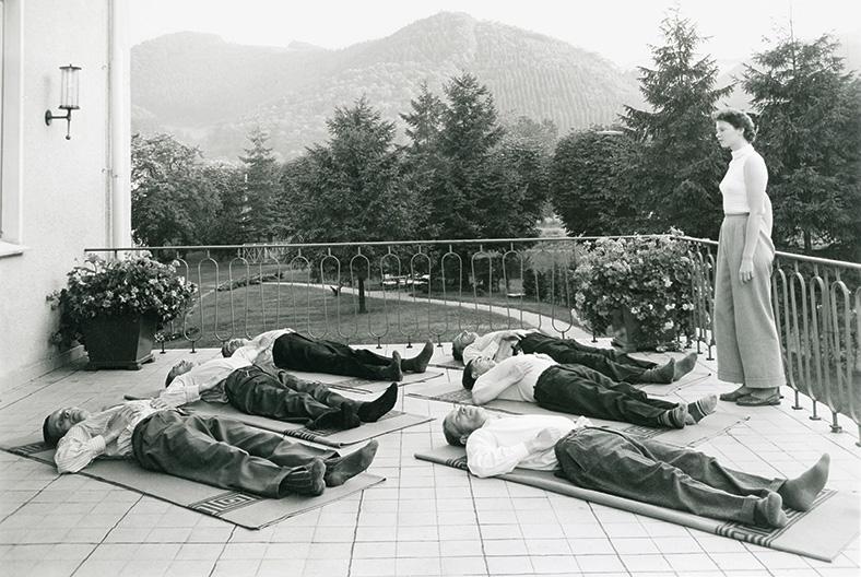 Mehrere Männer in hellen Hemden und Anzughosen liegen auf Decken auf einer Terrasse und haben die Hände auf ihren unteren Rippenbogen gelegt. Eine Frau in langer Hose und weißem Oberteil steht am Terrassengeländer und schaut auf die Gruppe.