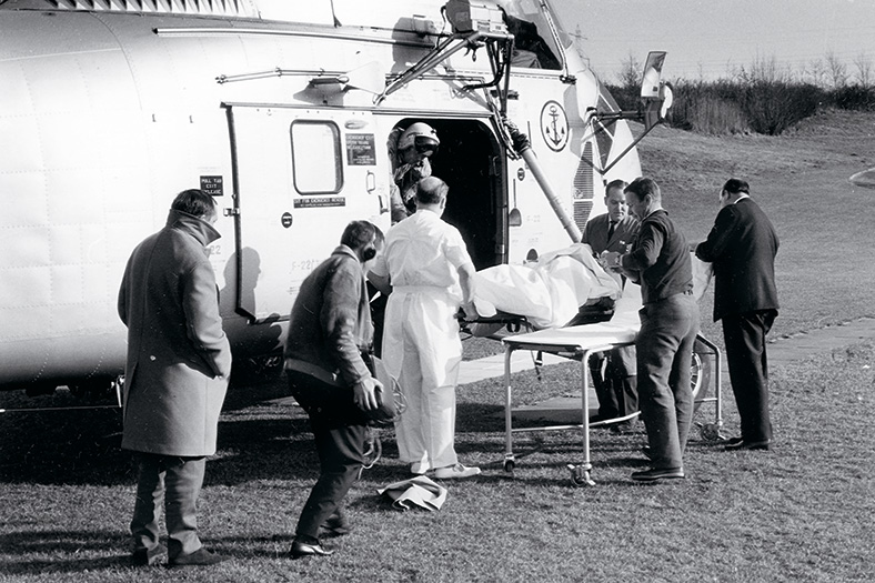 Schwarzweiß-Aufnahme eines Rettungshubschraubers, der mit einem Verletzten beladen wird, der auf einer Bahre liegt, mehrere Männer stehen darum herum.