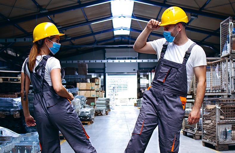 Zwei Kollegen - weiblich und männlich - in grauen Handwerker-Latzhosen, weißen T-Shirts und mit gelben Bauhelmen begrüßen sich ein einer Lagerhalle durch Berühren ihrer Schuhe. Sie tragen beide eine blaue Mund-Nasen-Schutzmaske.