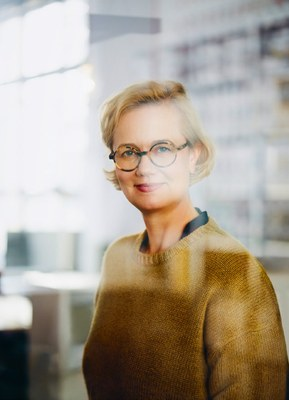 Porträt von Frau Borowski: Sie hat kürzere blonde Haare, trägt eine runde Brille, einen hellbraunen Pullover und schaut leicht lächelnd in die Kamera.