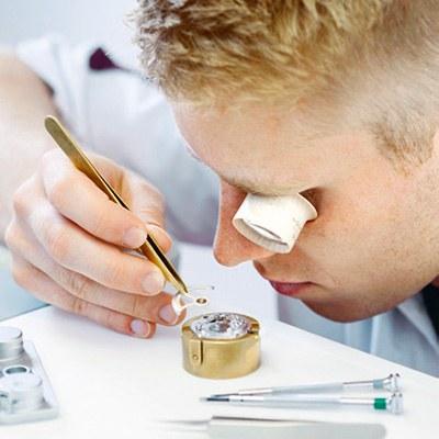 Ein junger Mann hat ein Vergrößerungsglas am Auge und arbeitet mit einer Pinzette an einer Uhr.
