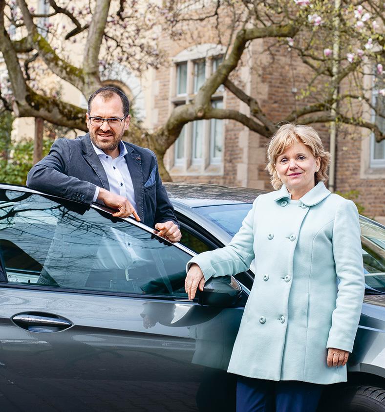Ein Mann und eine Frau stehen an ein dunkles Auto gelehnt und stützen sich beide auf die geöffnete Autotür. Der Mann trägt eine Brille, Vollbart, eine dunkle Jacke und ein helles Hemd, die Frau hat kürzere blonde Haare und trägt einen mintfarbenen Kurzmantel.