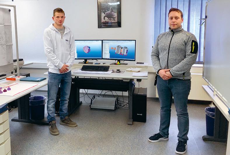 Zwei Männer stehen in einem Büro rechts und links von einem Schreibtisch, auf dem zwei Bildschirme stehen. Beide trage Hosen und eine Sweatjacke und haben die Hände vor dem Bauch zusammengelegt.