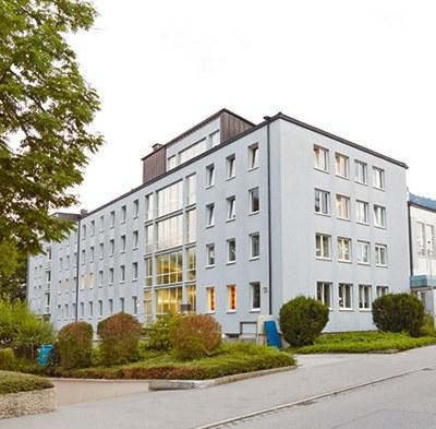 Ansicht der BG Klinik Bad Reichenhall. Ein weißes, mehrstöckiges Gebäude mit vielen Fenstern und Flachdach, umgeben von Büschen.