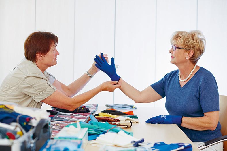 Schutzhandschuhberatung in der BG Klinik Bad Reichenhall. Eine Mitarbeiterin testet an einer Patientin einen blauen Handschuh. Beide sitzen sich gegenüber an einem Tisch voller bunter Handschuhe.