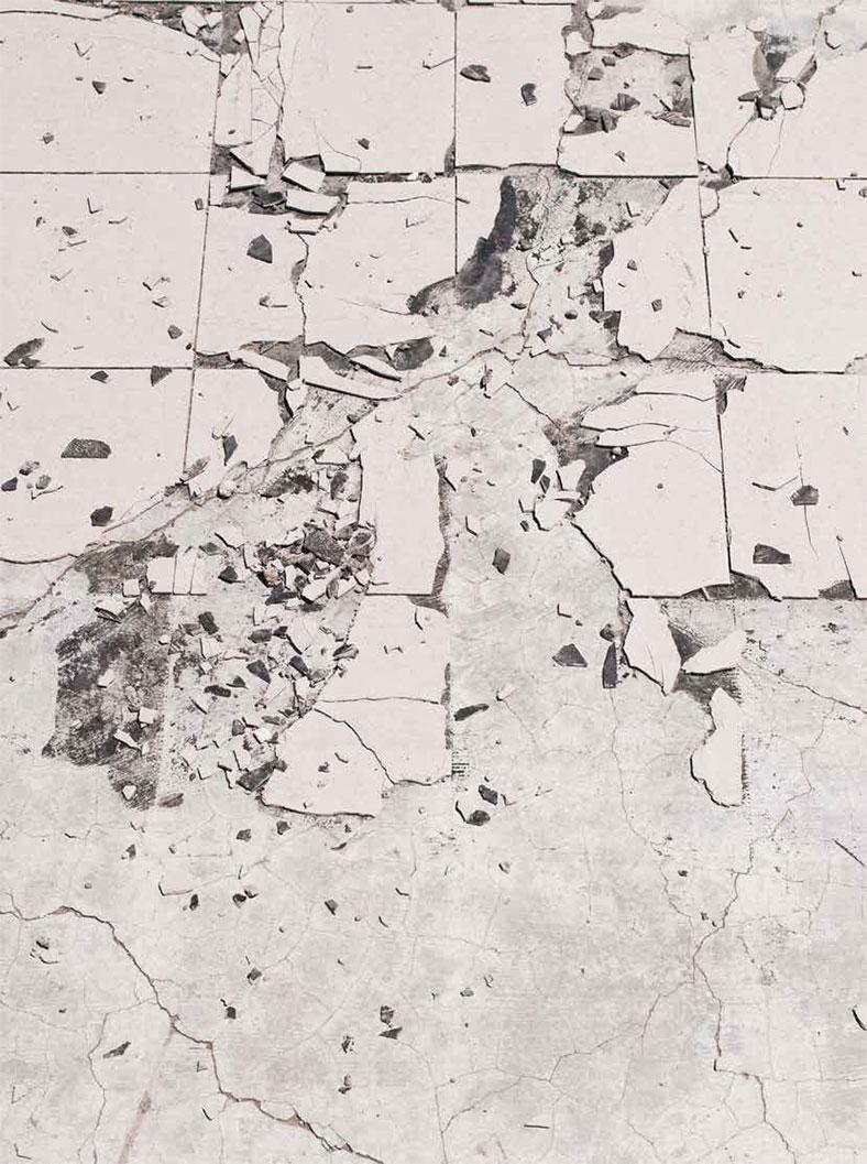 Boden mit zerbrochenen Fliesen in hellen Braungrau-Tönen.
