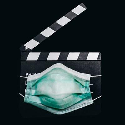 Atemschutzmaske in türkis ist vor eine schwarz-weiße Filmklappe gespannt, schwarzer Hintergrund.