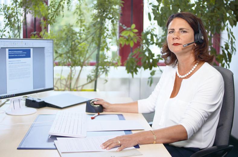 Frau sitzt mit Headset an einem Schreibtisch, vor sich Papiere. Sie trägt eine weiße Bluse und schaut in die Kamera.