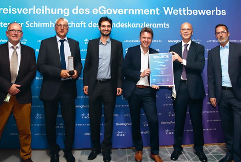 """Gruppe von Männern stehen nebeneinander vor einer blauen Wand mit der Aufschrift """"Preisverleihung des eGovernment Wettbewerbs""""."""